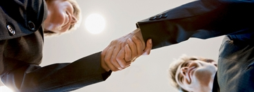 A businesswoman and a businessman shaking hands. The picture is taken from worm´ s eye view.